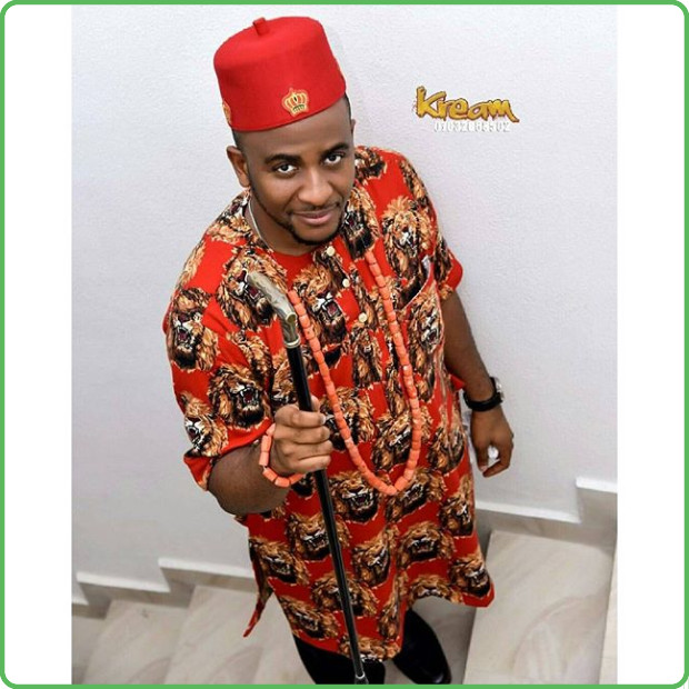 Young man wearing traditional igbo wears wearing red cap with and gold embroidering.