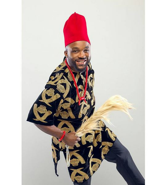 Inyanya wearing  a traditional igbo top- ISIAGU witha long red cap and holding horse tail staff