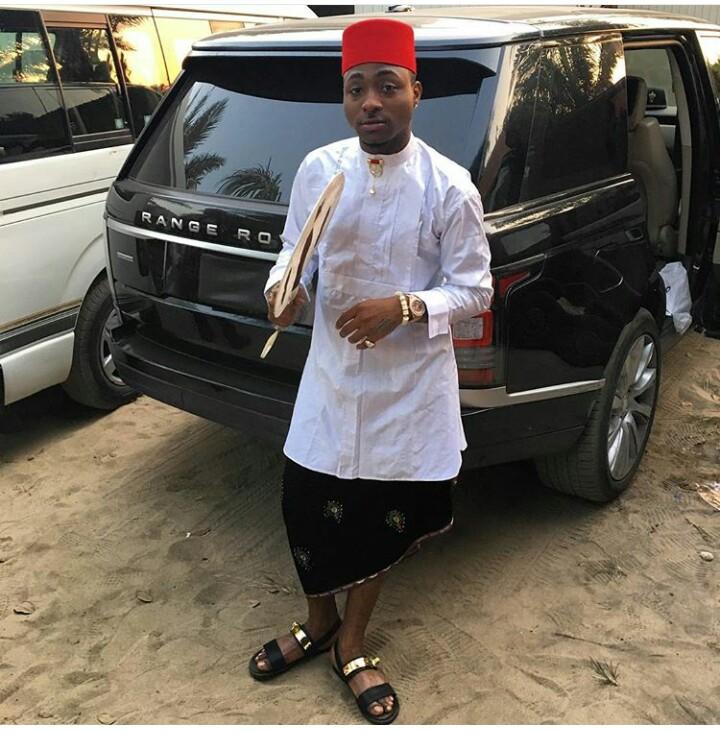 Davido wearing a white traditional igbo wear while tying igbo wrapper and wearing black sandal